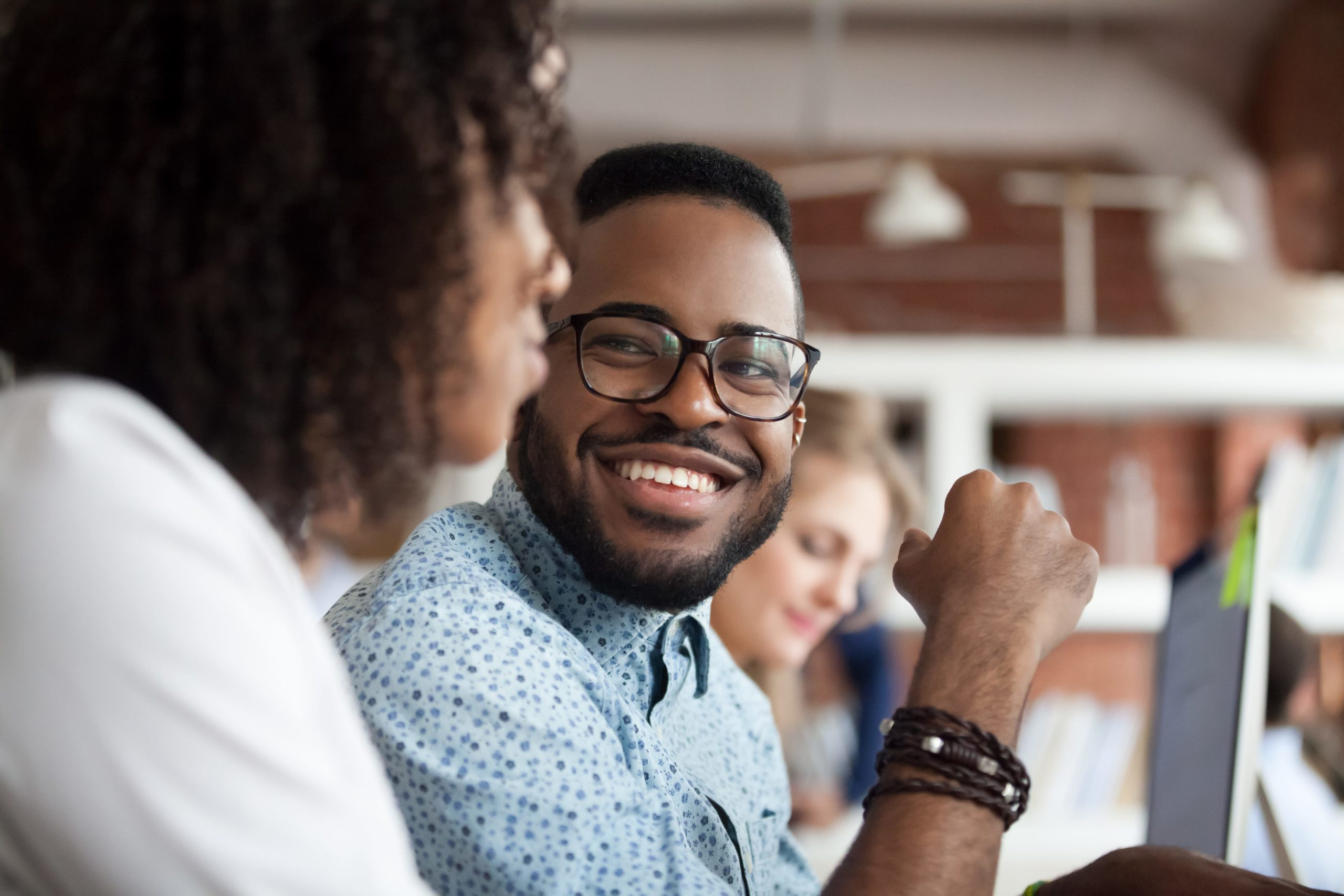 man with glasses smiling at colleague