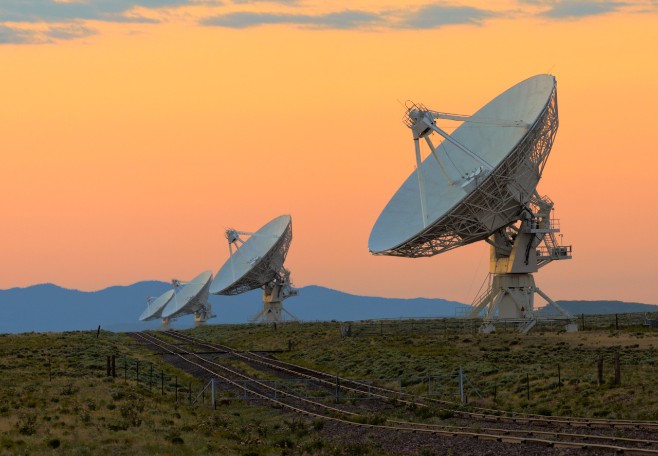 Row of large satelite dishesin a filed at sunset with rail tracks.