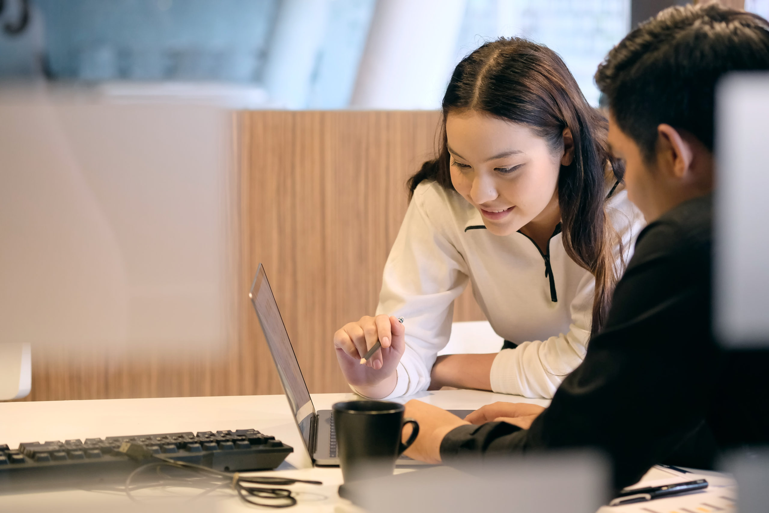 woman and man in office looking at laptop